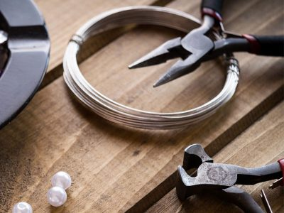 round nose pliers and silver wire with loose beads on a worktop